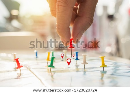 Soft focus hand holding paper pin on blur perspective road map, Red pin, point on the abstract noname map. Concept business background. #1723020724