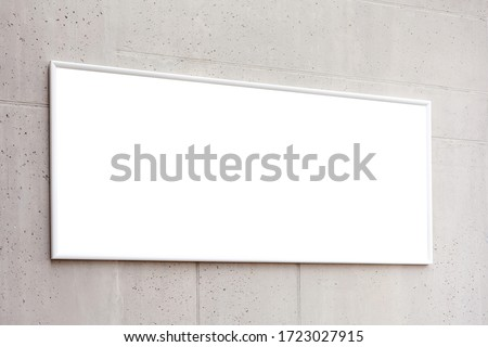 White blank horzontal poster frame, empty banner advertisement on a grey concrete wall inside the building, space for your text closeup Corporate business interior rectangle picture advert copy space