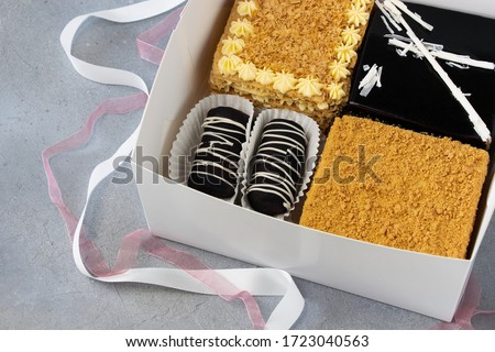 Set of cakes in white box with tapes decoration: Honey cake, Napoleon cake, Pigeon milk cake, Rum balls - Chocolate potatoes cakes. #1723040563