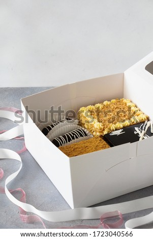 Set of cakes in white box with tapes decoration: Honey cake, Napoleon cake, Pigeon milk cake, Rum balls - Chocolate potatoes cakes. #1723040566