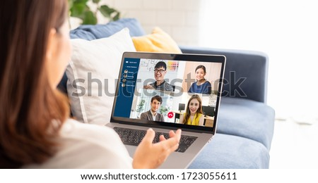 Young Asian businesswoman work at home and virtual video conference meeting with colleagues business people, online working, video call due to social distancing at home office Royalty-Free Stock Photo #1723055611