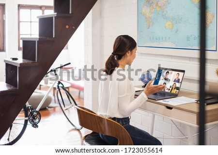 Young Asian businesswoman work at home and virtual video conference meeting with colleagues business people, online working, video call due to social distancing at home office Royalty-Free Stock Photo #1723055614
