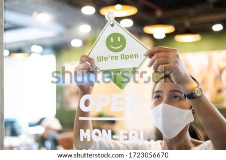 Business owner Asian woman wear protective face mask ppe hanging open sign at her restaurant / café, open again after lock down due to outbreak of coronavirus covid-19 #1723056670