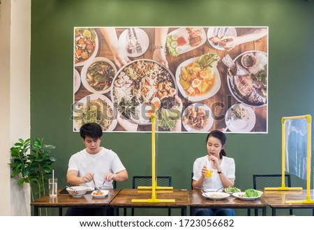 Asian man and woman sitting separated in restaurant eating food with table shield plastic partition to protect infection from coronavirus covid-19, restaurant and social distancing concept #1723056682