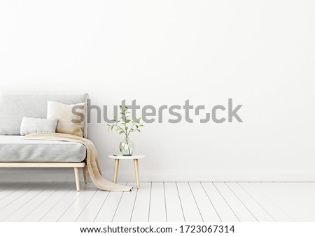 Interior wall mockup with empty white wall, gray sofa, beige pillows and green plant in vase. Free space on right.  3D rendering, illustration.