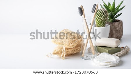 Zero waste, sustainable bathroom and lifestyle. Bamboo toothbrush, natural soap bar, loofah sponge, cotton pads, homemade DIY beauty products in reusable bottles over white background. Royalty-Free Stock Photo #1723070563