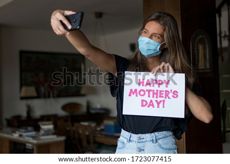 Girl wearing a mask is taking a selfie for mother's day during COVID-19.  #1723077415
