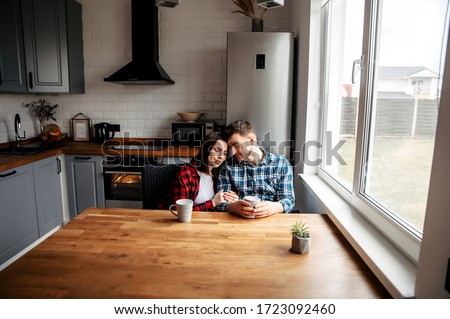 Love you so much. Couple in love in the kitchen of their home in the morning. They are sitting at the table and hugging, eyes closed with pleasure.