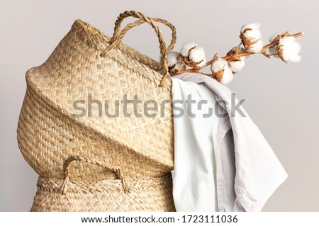 Straw wicker basket, natural cotton fabric, cotton flower branch on gray background. Bamboo basket stylish interior item eco design handmade. Decor of home. Natural eco materials, storage basket Royalty-Free Stock Photo #1723111036