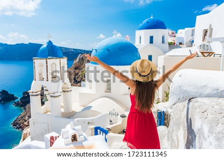 Europe travel happy vacation woman. Girl tourist having fun with open arms in freedom in Santorini cruise holiday, summer european destination. Red dress and hat person. #1723111345