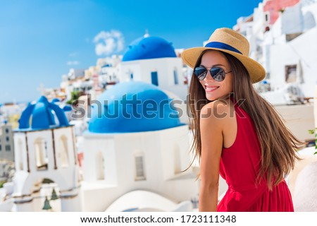 Europe Greece Santorini travel vacation woman on famous santorini Oia island travel destination. Happy young tourist girl in hat and sunglasses relaxing at blue dome church. Summer wanderlust. #1723111348