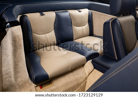 The back seats of a car with a beige and black leather cabin #1723129129