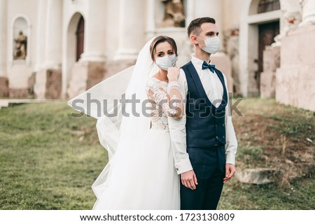 Young loving brides walking and hugging in the city near the church in medical masks with a bouquet of roses during quarantine on their wedding day. Coronavirus, disease, protection, illness, corona Royalty-Free Stock Photo #1723130809