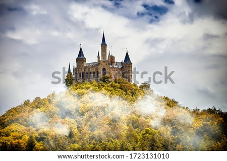 Castle on a wooded mountain in the fog under clouds, Hohenzollern, Germany Royalty-Free Stock Photo #1723131010