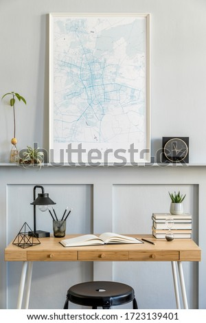 Stylish interior of home office room with black mock up poster map, wooden desk, black stool, clock, books, plants, cacti, office supplies, lamp and personal accessories in modern home decor.