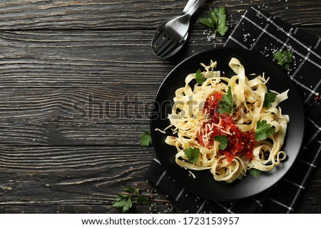Composition with plate of tasty pasta on wooden background #1723153957