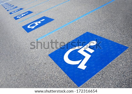 International handicapped symbol painted in bright blue on a shopping center parking space. The space is clearly marked on either side with additional white diagonal stripes.