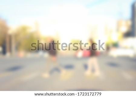 People cross the pedestrian lane during daylight hours for the background. An unfocused shot. Degradation. #1723172779