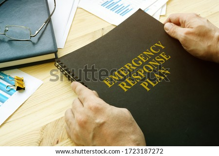 Man open disaster and emergency response plan for reading. Royalty-Free Stock Photo #1723187272