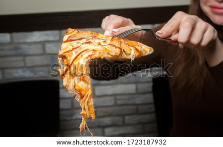 The girl takes a slice of pizza with a fork and knife #1723187932