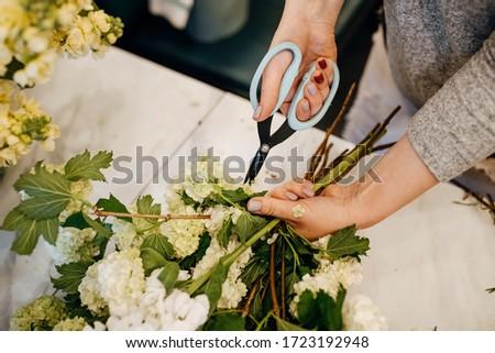 Process of making a bouquet of seasonal flowers. Female florist making bouquet in flower shop using scissors. #1723192948