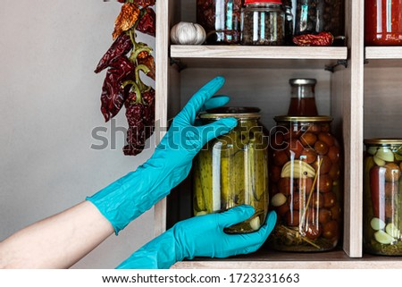 Homemade vegetables in jars on wooden shelves in the home pantry. Marinate food, as stocks from the autumn harvest, will be useful for self-isolation. Hands in blue gloves get one can with pickles. #1723231663