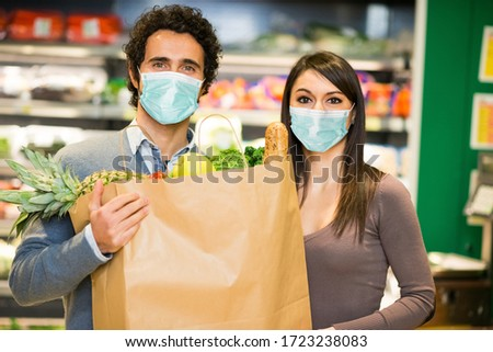 Masked couple holding a shopping bag full of food in a supermarket during coronavirus pandemic #1723238083
