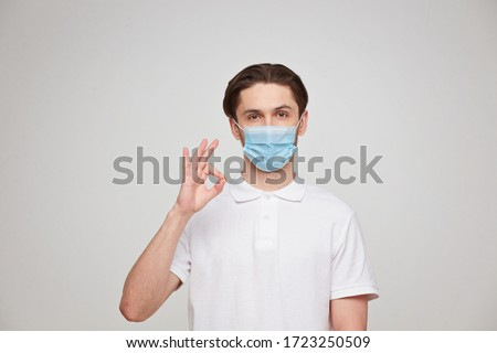 A man in a white T-shirt of European appearance in a medical mask, shows ok. In the mask you are protected from covid 19 viruses. Studio photo #1723250509