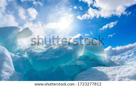 iceberg in calm sea with blue sky, sun rays and clouds #1723277812