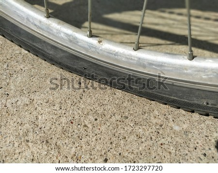 Flat tire on a bicycle. Wheel flattened on asphalt. The hole in the rubber tire. Aluminum Bicycle Wheel Frame #1723297720