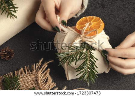 Zero waste and eco friendly christmas concept. Female hands wrap gifts in natural fabric with ornaments made of natural materials