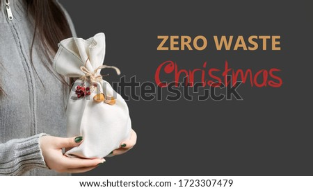 Zero waste and eco friendly christmas concept. Young woman holding in her hands wrapped in natural fabric. Lettering Zero Waste Christmas