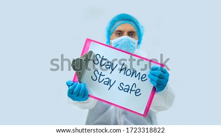 Doctor with face mask and blue gloves in background, holding a clipboard with white sheets with the message: STAY HOME, STAY SAFE in the foreground #1723318822