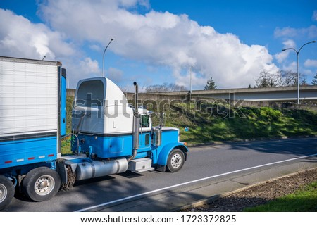 Powerful classic big rig diesel semi truck transporting food cargo in refrigerated semi trailer with refrigerator unit on the front wall running on the highway exit road with overpass intersection #1723372825