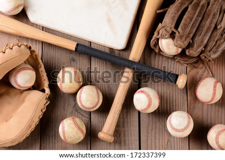High angle shot of old and use baseball equipment on a rustic wood surface. Items include, baseballs, bats, home plate, catchers mitt and glove. Royalty-Free Stock Photo #172337399