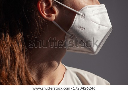 Young woman wearing KN-95 protection medical mask. Prevention of the spread of virus and epidemic, protective mouth filter mask. Diseases, flu, air pollution, corona virus concept Royalty-Free Stock Photo #1723426246
