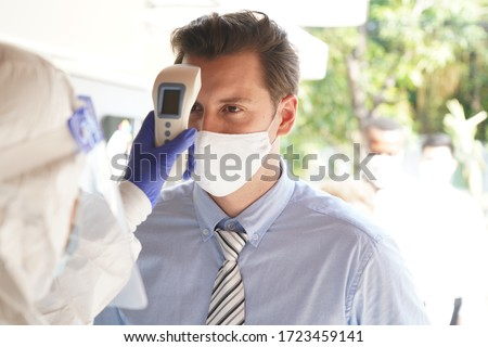Disease control experts  use an Infrared thermometer equipment to check the temperature on the forehead and use alcohol gel to screen the patients addicted to Covid before entering the building. Royalty-Free Stock Photo #1723459141