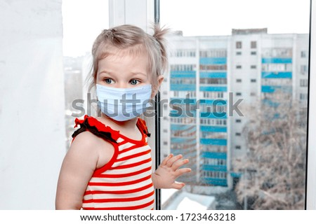 Little cute girl stands on the windowsill of a high-rise building during. #1723463218