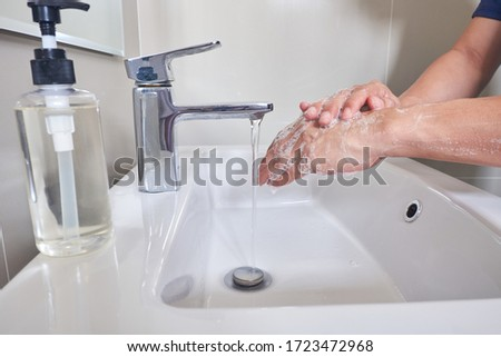 Washing hands with soap in hot water at bathroom sink man hand hygiene for coronavirus pandemic precaution. #1723472968