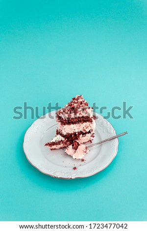 Piece of cake on vintage festive white plate with monograms and gold border on blue background. Spoon with small piece of cake in it. Homemade sponge cake with sour cream. Eating process. Vertical.