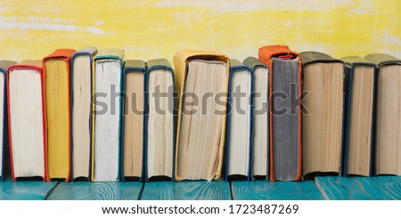 Composition with vintage old hardback books, diary, fanned pages on wooden deck table and red background. Books stacking. Back to school. Copy Space. Education background. #1723487269