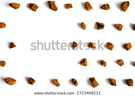 chaga mushroom. broken pieces of birch tree chaga mushroom for brewing natural medicinal antitumor and antiviral detox tea, isolation on white background. regular pattern. space for text #1723488211