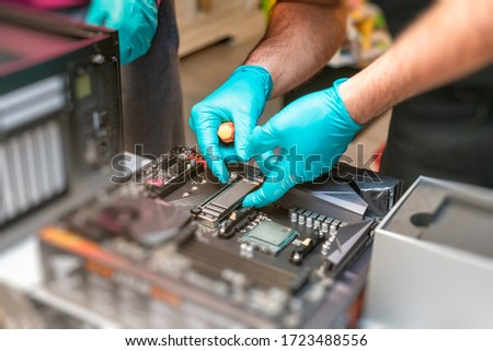 Personal computer technicians mounting ssd drive on the motherboard socket, pc assembling. #1723488556