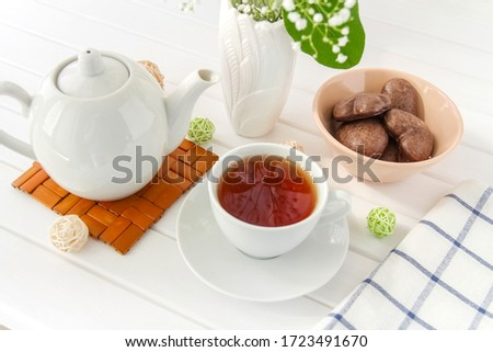White ceramic cup and tea pot, vase with flowers and cookies on white wooden table background. Beautiful setting the table for Breakfast and tea time. The concept of Beginning of the day good morning.