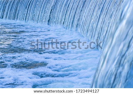 Beautiful city waterfall with blue water and foam #1723494127