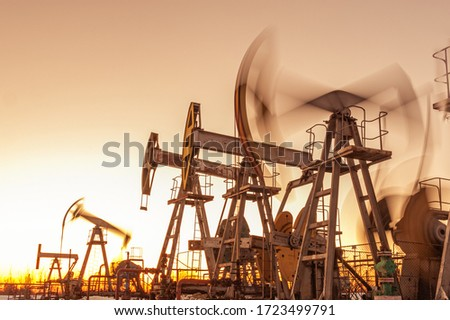 Oil pump rig. Oil and gas production. Oilfield site. Pump Jack are running. Drilling derricks for fossil fuels output and crude oil production. War on oil prices. Global coronavirus COVID 19 crisis. #1723499791