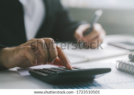 Close up businessman hand using calculator and writing make note with calculate about finance accounting.finance accounting concept #1723510501