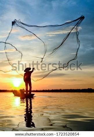 Fisherman throwing out fishing net on the lake. Fisherman throwing net at sunrise Royalty-Free Stock Photo #1723520854