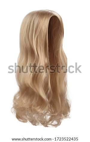 Subject shot of a natural looking caramel blonde wig without bangs. The long wig with wavy strands is isolated on the white background.  Royalty-Free Stock Photo #1723522435