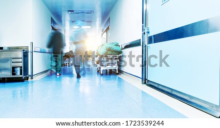 Doctors or nurses walking in hospital hallway, blurred motion. Royalty-Free Stock Photo #1723539244
